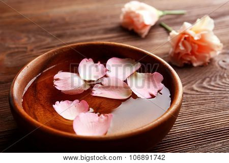 Pink rose petals in a bowl of water on wooden background