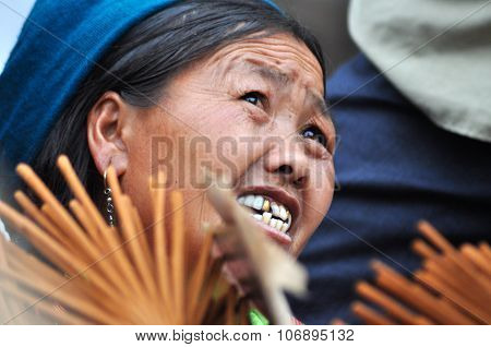 Hmong Woman Selling Incense Sticks In Bac Ha Market, Vietnam
