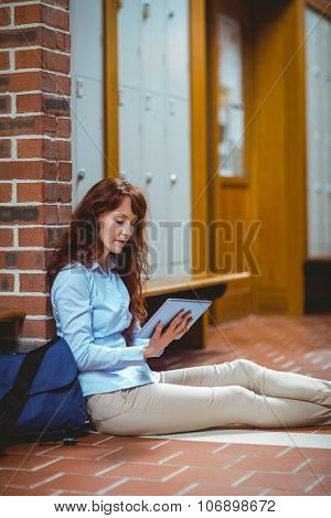 Mature student using tablet in hallway at the university