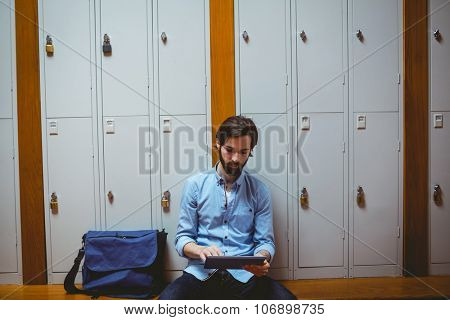 Hipster student using tablet in hallway at the university