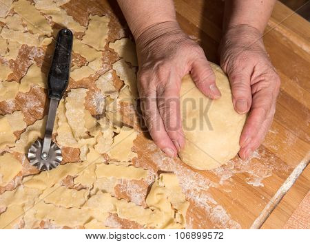 Woman Kneading Dough On A Table In The Kitchen