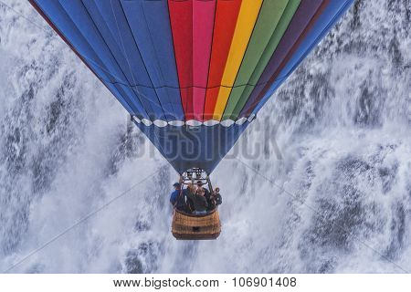 Hot Air Balloon Decending In Front Of A Waterfall