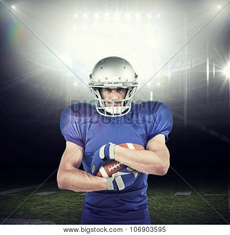 Portrait of sportsman holding ball against american football arena