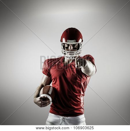 American football player pointing at camera against grey vignette