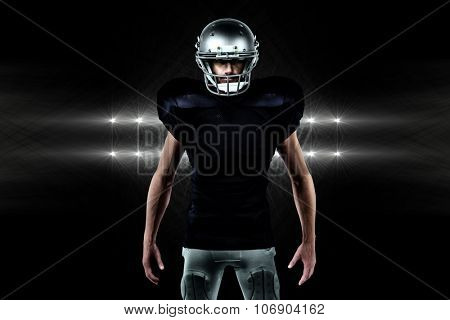 Portrait of confident sports man standing against spotlights