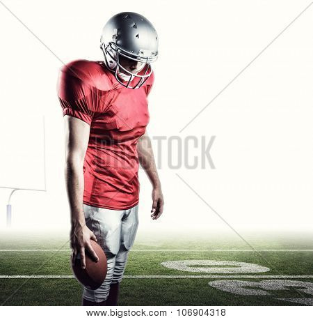 American football player with ball looking down against american football posts