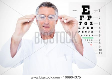 Optician in coat holding glasses against eye test