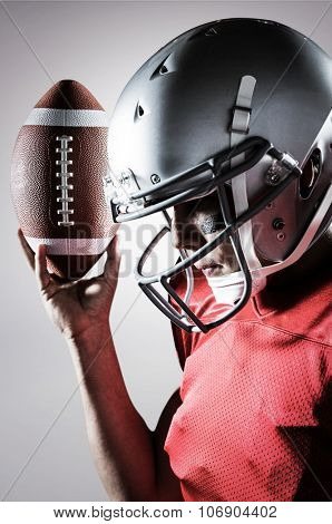 Sportsman looking down while holding American football against grey background