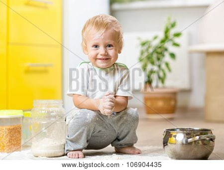 Playful child boy with face in flour surrounded kitchenware and foodstuffs