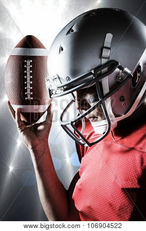 Sportsman looking down while holding American football against spotlights