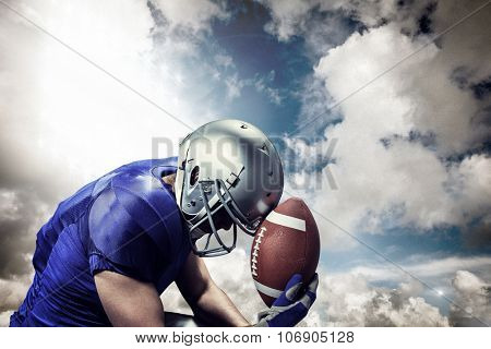 Upset American football player with ball against spotlight in sky