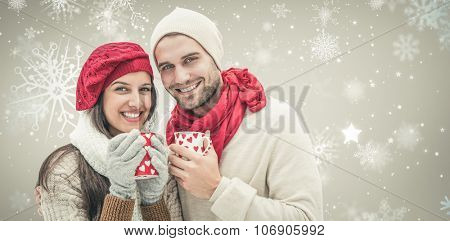 Winter couple holding mugs against snowflake pattern