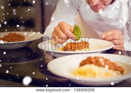 Snow against closeup of a male chef garnishing food