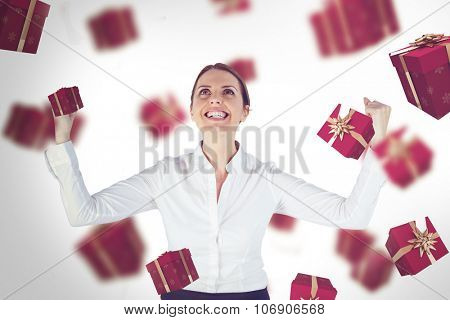 Successful businesswoman with clenched fists looking up against red presents