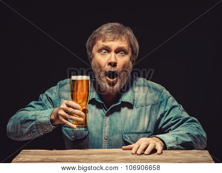 The enchanted and emotional fan with glass of beer