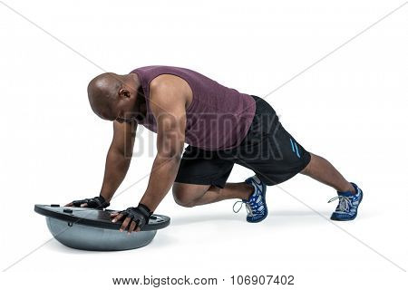 Fit man exercising with bosu ball on white background