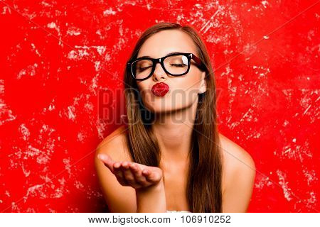 Pretty Girl With Glasses Sending A Kiss Against The Red Background
