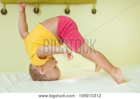 Toddler boy doing exercises in child room