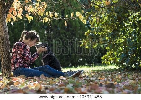 Young Woman Sitting Under A Coulourful Autum Tree Lovingly Petting Her Black Dog