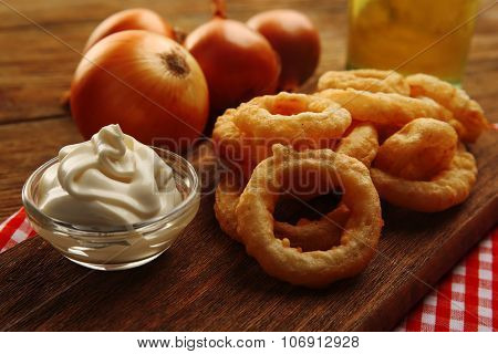 Chips rings with sauce and onion on cutting board closeup