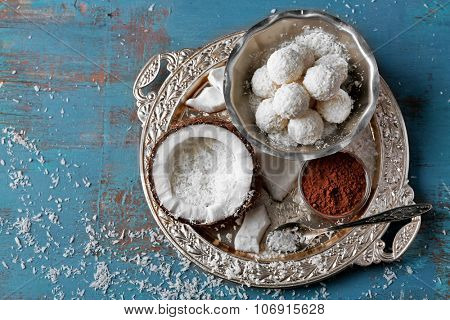 Homemade candies in coconut flakes and ingredients on color wooden background