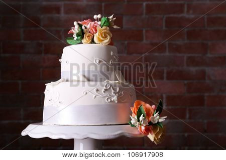 Beautiful wedding cake decorated with flowers on brick wall background, close up