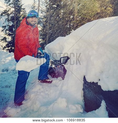 Winter, man is shoveling the car of snow