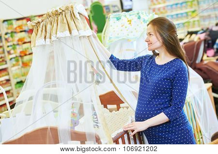 Pregnancy shopping. Pregnant woman choosing cradle cot or crib for newborn at baby shop store