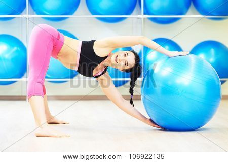 Smiling young woman doing warm up fitness ball exercise routine in sport club