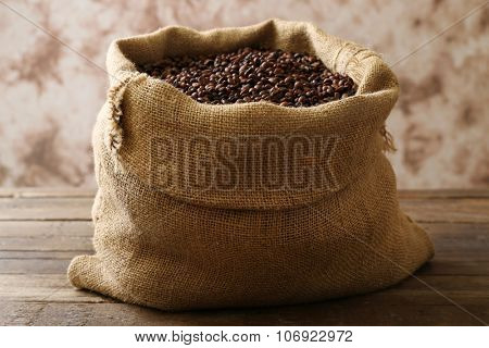Sac with roasted coffee beans on wooden table