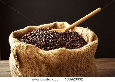 Sac with roasted coffee beans with spoon on wooden table in front of dark background