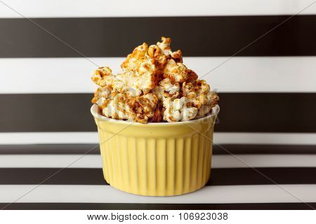 Sweet caramel popcorn on striped black and white background