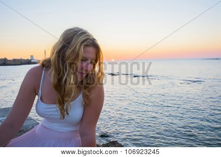 Pretty Female Model Looking At The Waves After Sunset