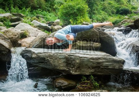 Young sporty fit woman doing yoga asana Eka Pada Koundinyasana 1 at tropical waterfall