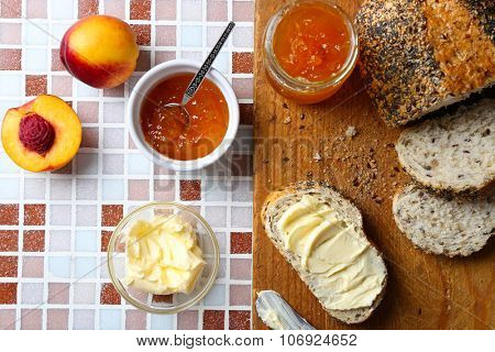 Tasty jam in the jar and bowl, ripe peaches, bread with butter and wooden tablet on mosaic background