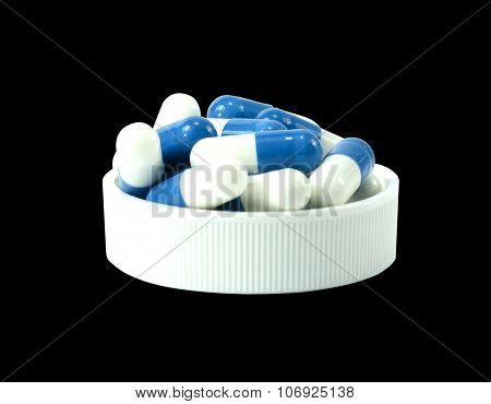 Some Pills Of A White And Blue Colors In A White Lid Of Jar