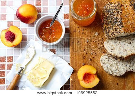 Tasty jam in the jar and bowl, ripe peaches, butter, fresh bread and wooden tablet on mosaic background close-up