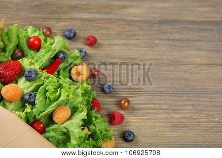Beautiful bouquet of lettuce and berries in paper sheath on wooden background, close up