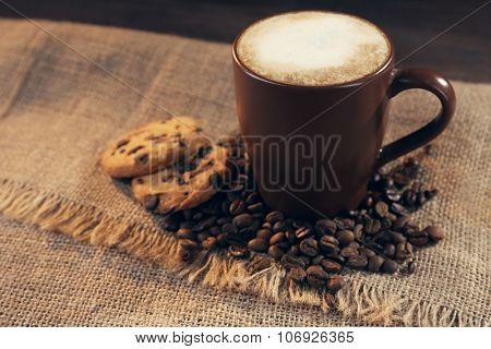 Cup of coffee with roasted coffee beans around and biscuit on Hessian on wooden  background