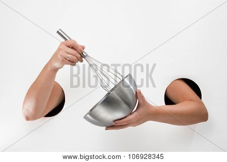 Female  hands through the holes on a white background are holding a whisk and mixing bowl