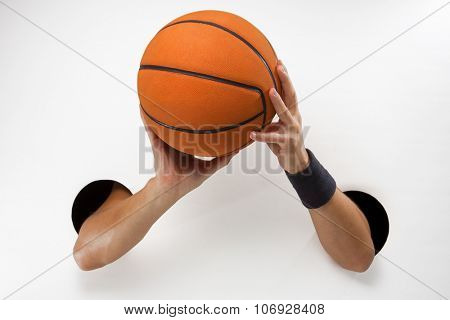 Male  hands through the holes on a white background are holding the basket ball before throwing