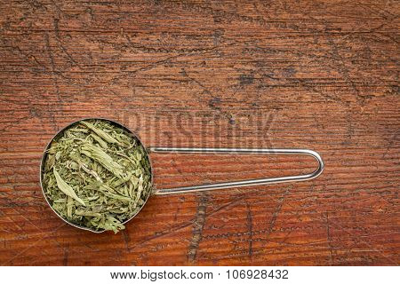 stevia dried leaves in a metal measuring scoop against rustic wood - natural sweetener, sugar substitute