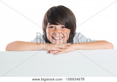 Young boy leans over poster. Happy cute kid leaning on blank white poster. Closeup of smiling boy leaning on empty grey placard and looking at camera isolated on white background.