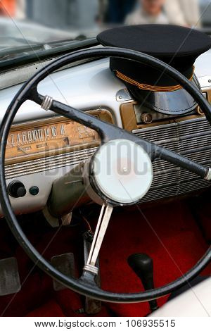Dashboard Of Old Car With Steering Wheel And Cap Of Driver