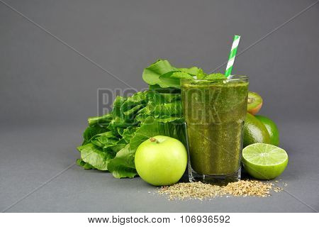 Green healthy juice with fruits and herbs on gray background