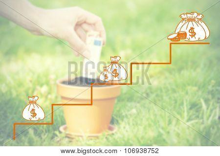 Money concept.Female hand planting money into flowerpot