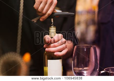 Opening a wine bottle with corkscrew