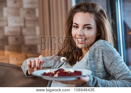 Beautiful smiling girl eating delicious dish