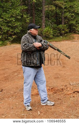 Hunter demonstrating the cradle carry method to safely carry a firearm while hunting, the choice of the correct method depends on the situation