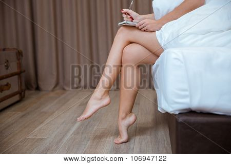 Beautiful legs. Close-up of young woman sitting on the bed